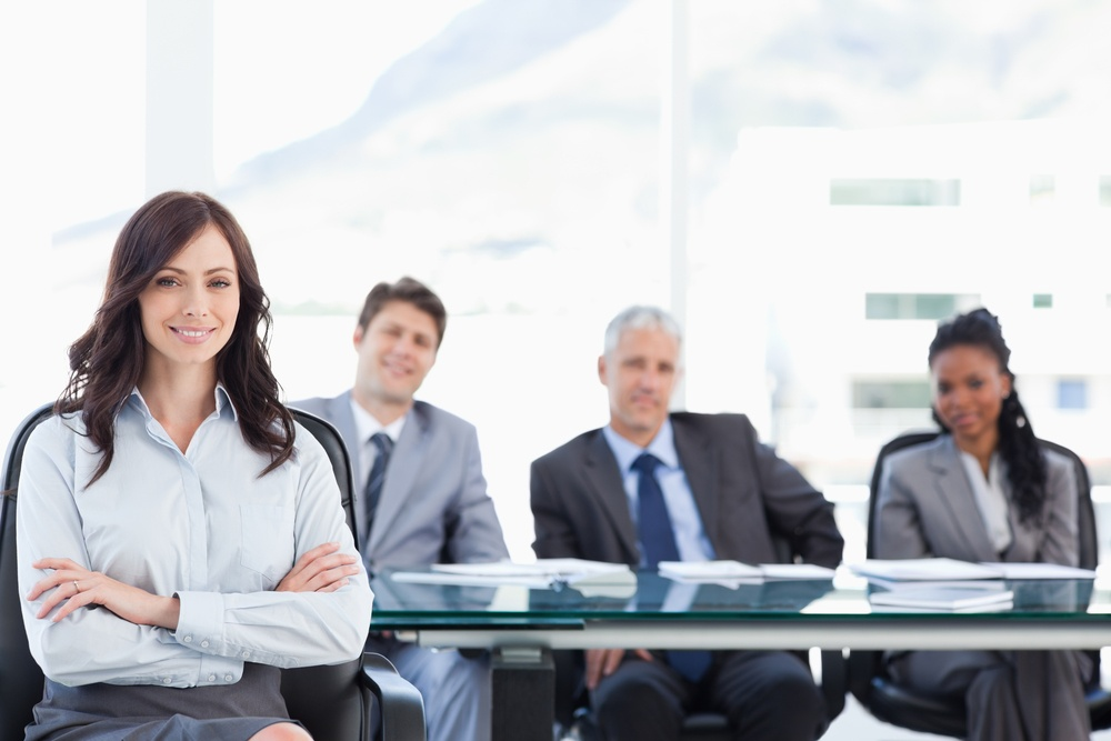 Smiling businesswoman sitting and crossing her arms while accompanied by her team.jpeg