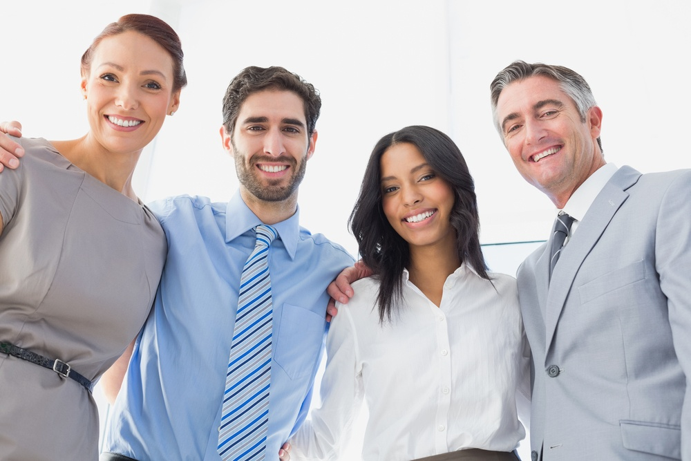 Smiling employees standing all together at work.jpeg